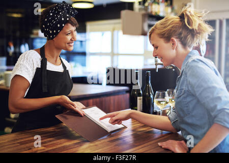 Female customer choosing wine from a wine list being presented to her by a charming young African American bartender - Stock Photo
