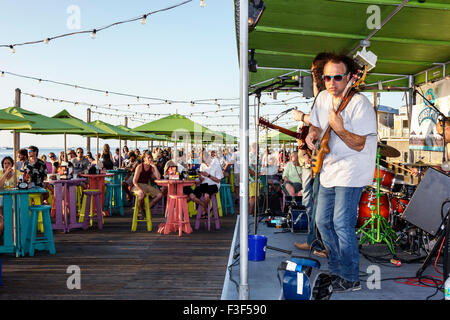 Key West Florida Keys Sunset Pier bar restaurant stage live music musician man band playing guitar audience - Stock Photo