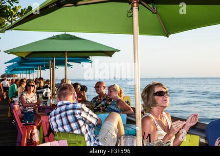 Key West Florida Keys Sunset Pier bar restaurant tables umbrellas - Stock Photo