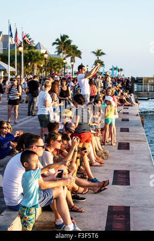 Key West Florida Keys Mallory Square Dock sunset celebration festival Asian boy families family watching - Stock Photo