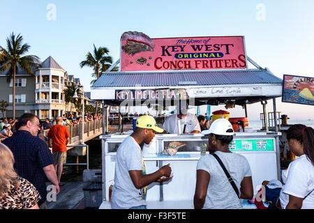 Key West Florida Keys Mallory Square Dock sunset celebration festival food vendor conch fritters sale Black man - Stock Photo