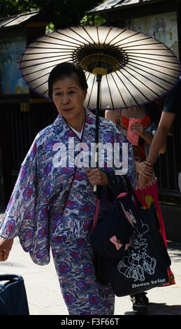 A Japanese woman dressed in a traditional Kimono holding a traditional Japanese umbrella. - Stock Photo