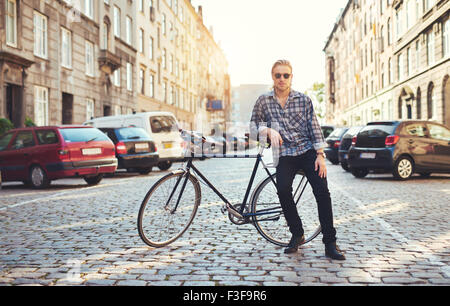 Living in the city, portrait of young man sitting on his bike - Stock Photo