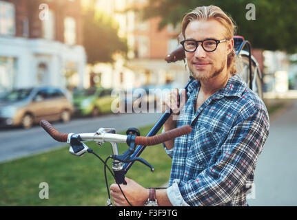 Portrait of blonde white man in the city with a bike - Stock Photo