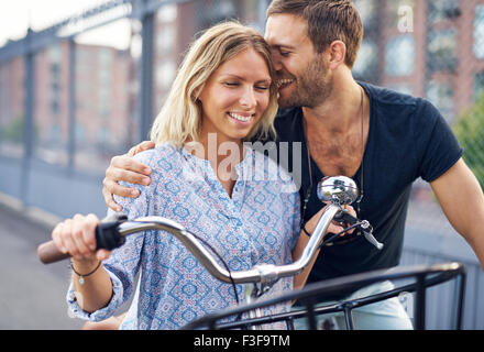 City couple loving each other while out riding bikes - Stock Photo