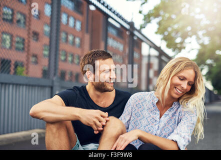Man teasing his girlfriend, big city couple in a park - Stock Photo
