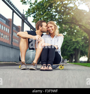 Man kissing woman on her cheek while sitting in a park - Stock Photo