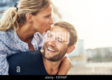 Woman Kissing Man While He Laughs, Young Couple - Stock Photo