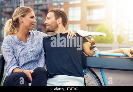 Loving couple sitting on bench in a city environment - Stock Photo