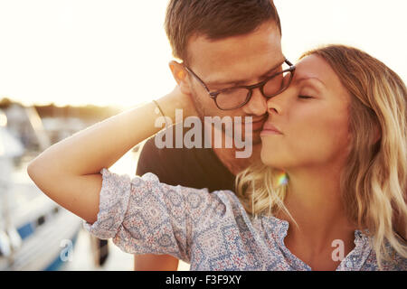 Couple Kissing On A Summer Evening, Blonde Woman and Man with Glasses - Stock Photo