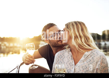 Husband and Wife Kissing Sitting on a Boat - Stock Photo