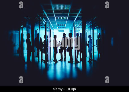 Group of co-workers interacting at meeting in corridor of business center - Stock Photo