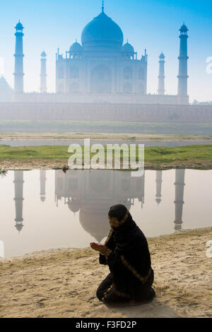 A Muslim woman offering namaz front mogul monument Taj Mahal seven wonder world constructed emperor Shah Jahan Agra - Stock Photo