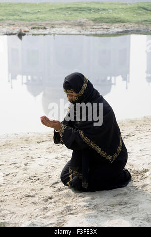 Muslim woman offering namaz front mogul monument Taj Mahal seven wonder world constructed by emperor Shah Jahan - Stock Photo