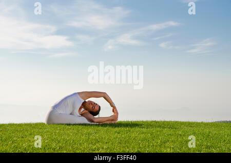 Young woman practising Hatha-Yoga outdoor, showing the pose  variation of pashchimottanasana,  variation of sitting - Stock Photo