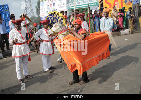 Kachi Ghodi ; Men standing in dummy horse and performing Ranjasthani dance wearing maratha costume religious procession - Stock Photo