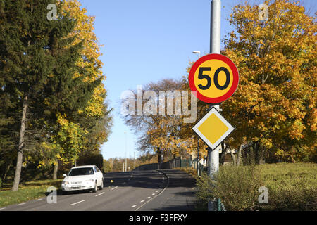 White car on road also sign board speed limit 50 ; Skepplanda ; Sweden ; Scandinavian - Stock Photo