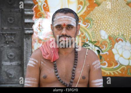 Religious preacher wearing rudraksha mala applying holy ash bhasma body standing Adi Shankaracharya temple Kaldi - Stock Photo