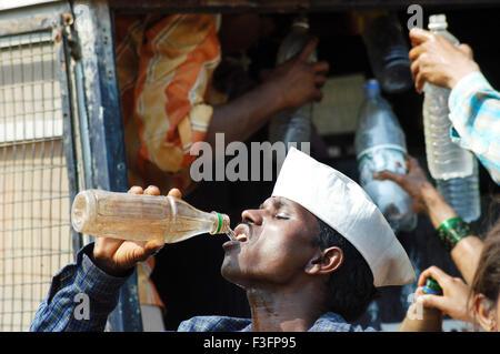 Man quench his thirst by drinking water form plastic bottle ; Bombay Mumbai ; Maharashtra ; India - Stock Photo