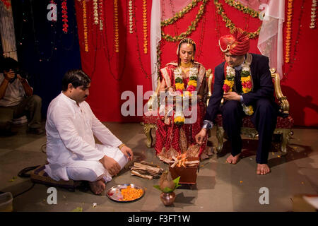 Pundit chanting mantra and bride and bridegroom offering in holy fire in marriage ceremony MR Bridegroom#729E;NO - Stock Photo