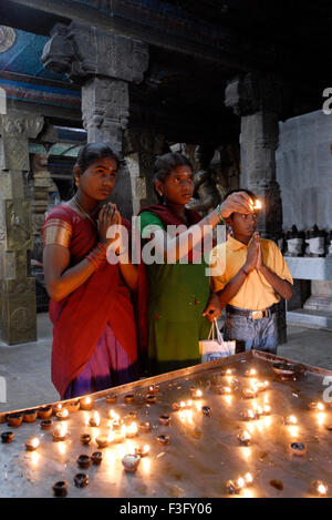 Women worshipping by lighting oil lamps in Swaminatha Swami temple ; Swamimalai ; Tamil Nadu ; India - Stock Photo