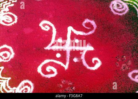Swastika symbol of sun god colourful rangoli designs drawn with coloured powder on floor - Stock Photo