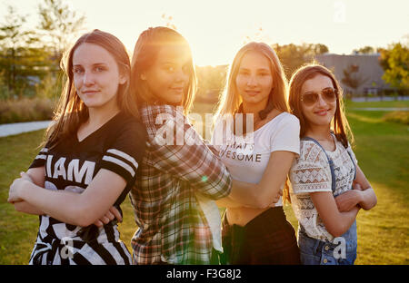 Four friends standing outside, posing for the camera, sun flare - Stock Photo