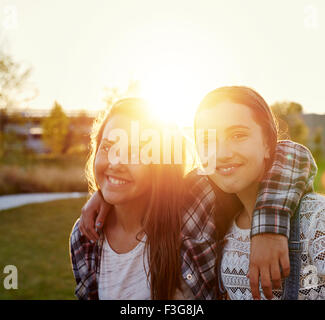 Two teenage girls outside on a summer evening in sun flare - Stock Photo