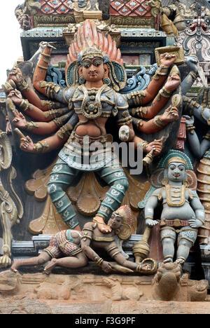 decorated painted stucco figures goddesses killing demon gopuram Shree Meenakshi Sundareswarar temple Madurai Tamil - Stock Photo