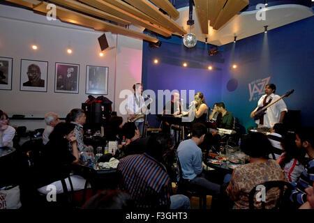 People enjoying live band performance at a popular restaurant not just jazz by the bay ; Mumbai Bombay ; Maharashtra - Stock Photo