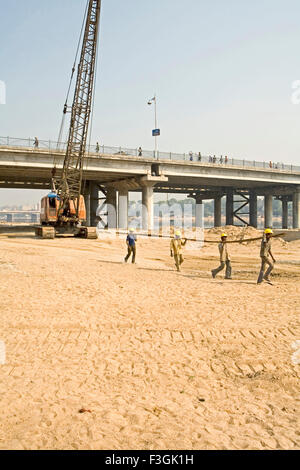 Construction workers manually transporting iron bars at a construction site on Sabarmati river ; Ahmedabad ; Gujarat - Stock Photo