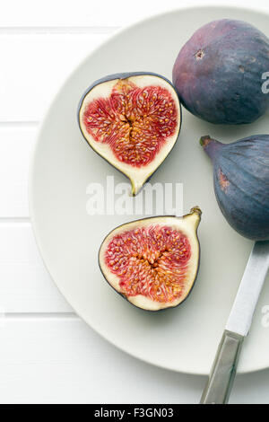 sliced fresh figs on plate with knife - Stock Photo