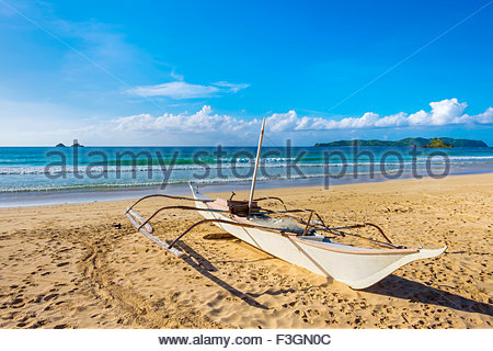 Small outrigger boat on the beach at Nacpan Beach, El Nido, Palawan, Philippines - Stock Photo