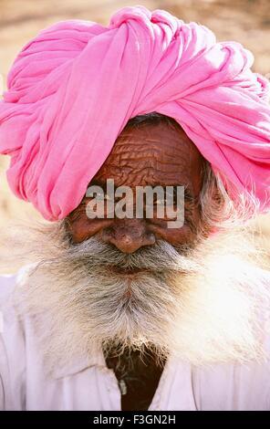 Portrait of old beard man wearing pink headgear - Stock Photo