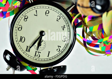 close up of  a black retro alarm clock, around midnight, with paper streamers and cork from a bottle of sparkling - Stock Photo