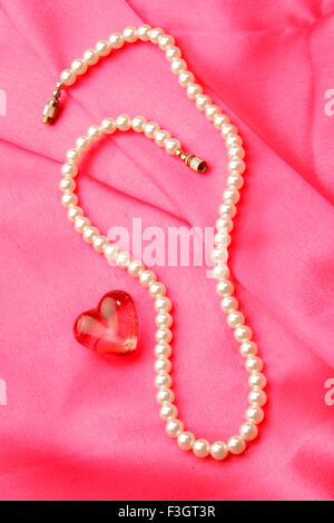 Jewellery in form pearl necklace with synthetic red gem stone of heart shape against pink satin background - Stock Photo