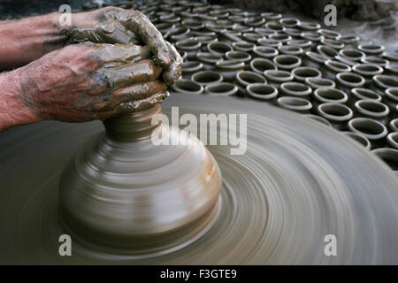Potter's fingers moulding earthen pot on wooden turning wheel wet clay several laid already prepared drying Pune - Stock Photo