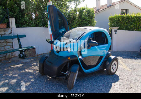 Blue twizy parked in front of a house with an open door - Stock Photo