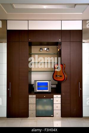 Interior of house ; television with guitar ; Mulund ; Bombay Mumbai ; Maharashtra ; India - Stock Photo
