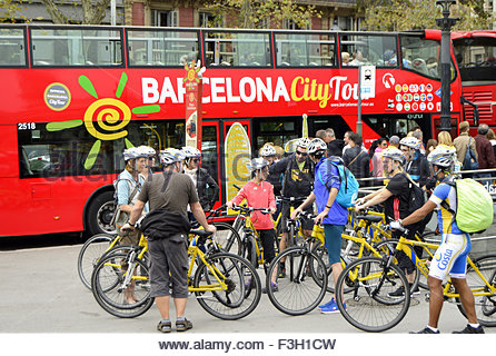 Tourists on bicycles and city tour bus at Placa de Catalunya in Barcelona Spain Europe - Stock Photo