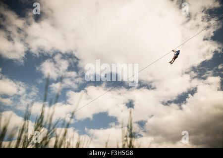 Mature man on zip wire over field - Stock Photo