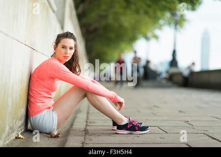 Portrait of young female runner sitting along riverside - Stock Photo