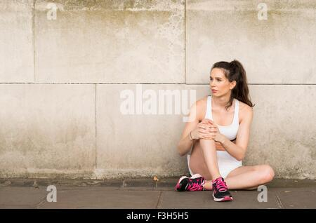 Young female runner sitting on sidewalk looking sideways - Stock Photo