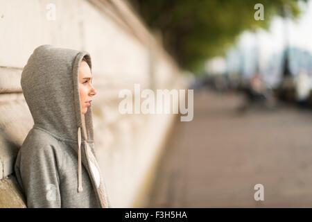 Young female wearing grey hoody looking out from riverside - Stock Photo