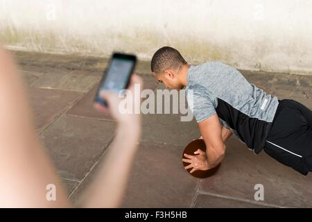 Over shoulder view of trainer timing male runners push ups on smartphone - Stock Photo