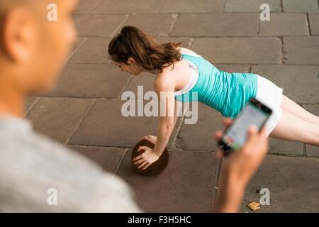 Over shoulder view of trainer timing female runners push ups on smartphone - Stock Photo