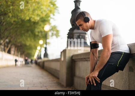 Young male runner wearing headphones taking a break on riverside - Stock Photo