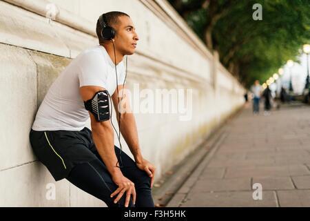 Male runner wearing headphones taking a break on riverside - Stock Photo