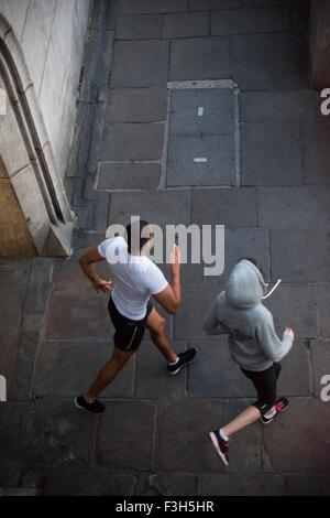 Overhead view of male and female runners running in city - Stock Photo