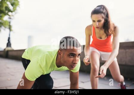 Young female trainer with male runner on riverbank - Stock Photo